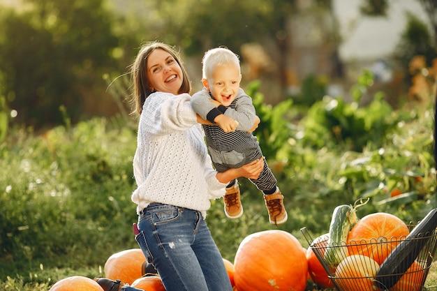 Madre e figlio che si siedono su un giardino vicino a molte zucche
