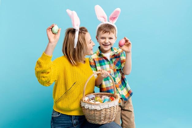 Madre e figlio che tengono uovo dipinto