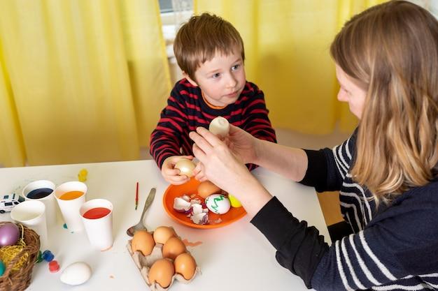 Madre e figlio colorare le uova per pasqua