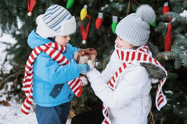 Madre e figlio decorano l'albero di natale all'aperto in un parco invernale,