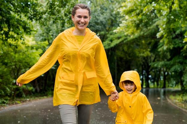 Madre e figlio di vista frontale che si tengono per mano mentre indossando i cappotti di pioggia