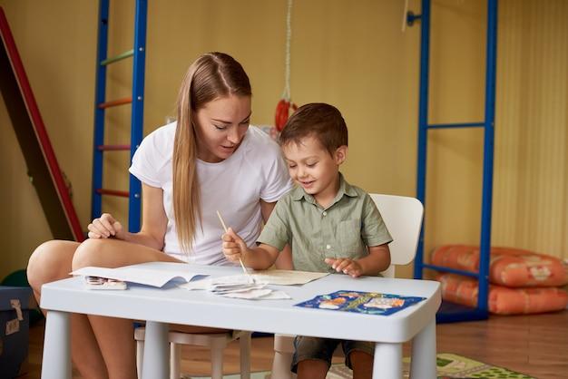 Madre e figlio disegnano a un tavolo all'interno della stanza.