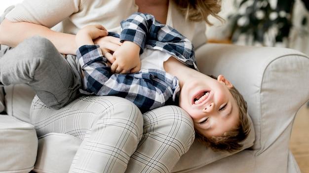 Madre e figlio giocano insieme sul divano