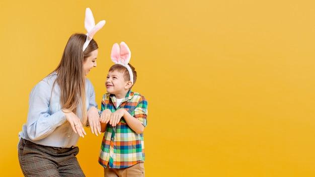 Madre e figlio imitando coniglio con copia-spazio