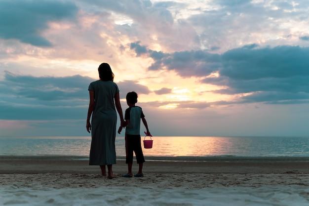 Madre e figlio in piedi sulla spiaggia guardando il tramonto