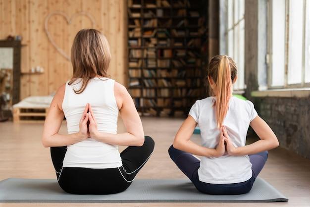 Madre e figlio meditando su stuoie di yoga