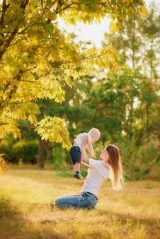 Madre e figlio nella foresta d'autunno giocano