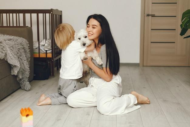 Madre e figlio piccolo si divertono a casa con il cane