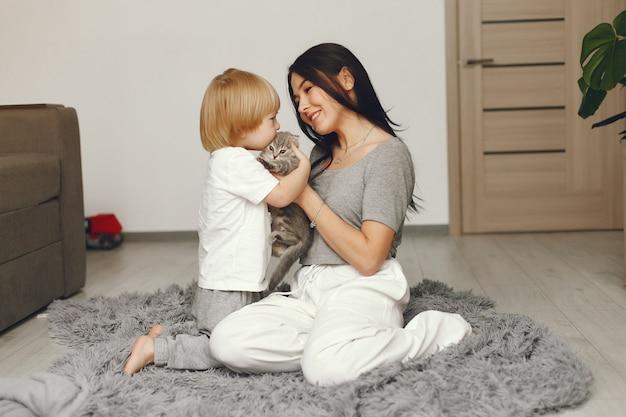 Madre e figlio piccolo si divertono a casa con un gatto