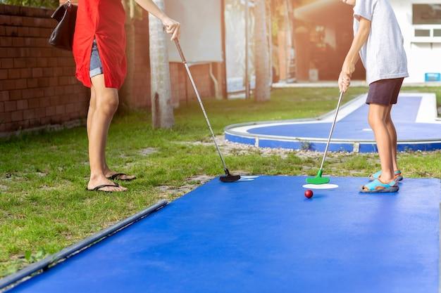 Madre e figlio ragazzo giocando a mini golf