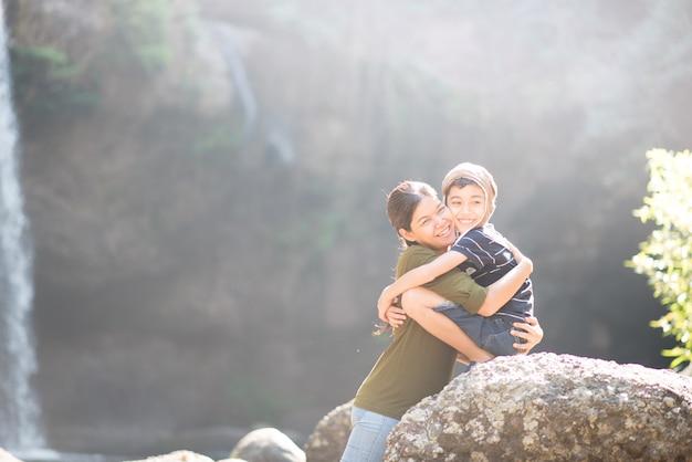 Madre e figlio si abbracciano felici insieme nella foresta