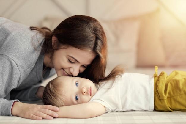 Madre e figlio sul letto, mamma bacia suo figlio, sentimenti, relazione di madre e figlio,