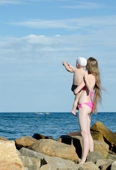Madre e figlio sulle mani sono tra le pietre sulla riva del mare, mostrano in lontananza