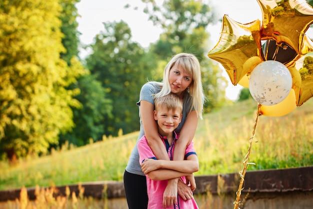 Madre e il suo piccolo figlio con palloncini d'oro in giornata estiva.