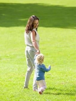 Madre e neonata che camminano sull'erba