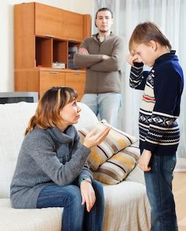 Madre e padre che rimproverano il figlio nel soggiorno