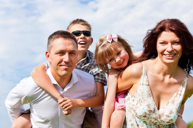 Madre e padre che trasportano i bambini sulle spalle