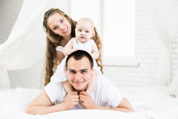 Madre e padre con piccolo bambino in un letto