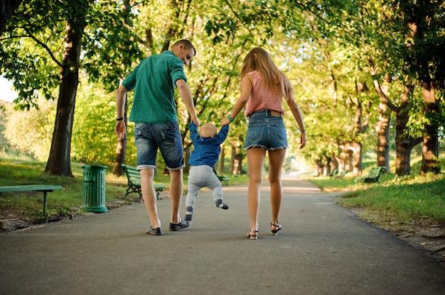 Madre e padre con un bambino che cammina nel parco verde