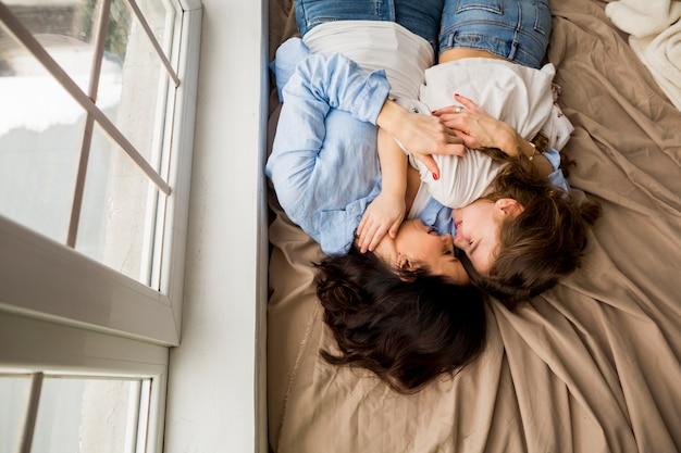 Madre e piccola figlia che abbracciano sul letto