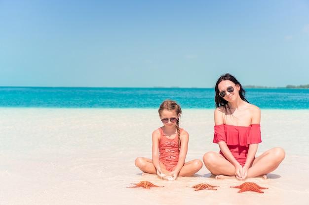 Madre e piccola figlia che godono del tempo alla spiaggia tropicale