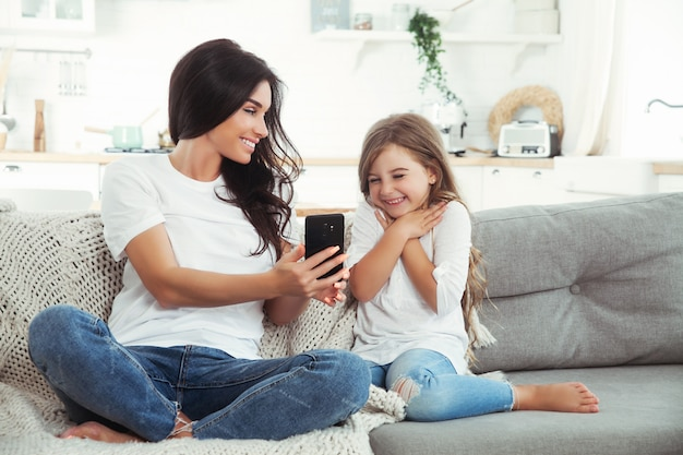 Madre e piccola figlia sorridenti che giocano con lo smartphone