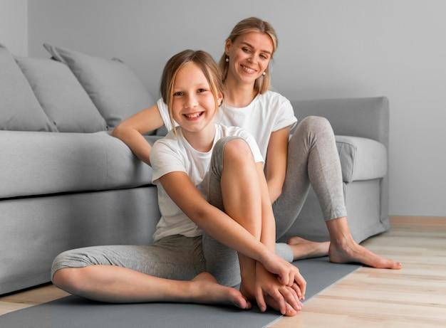 Madre e ragazza a casa sulla stuoia