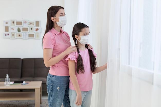 Madre e ragazza guardando fuori dalla finestra