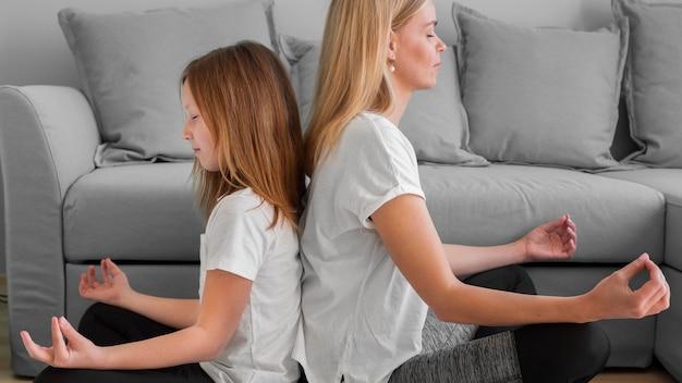 Madre e ragazza nella posa di yoga