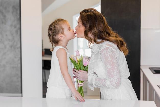 Madre e ragazza si baciano con fiori di tulipano in possesso