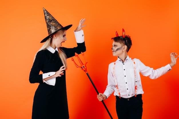 Madre e sole nel trucco del diavolo mascherato si spaventano a vicenda. halloween