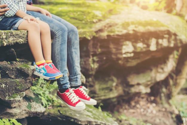 Madre e suoi piccoli piedini figlio seduto alla scogliera.