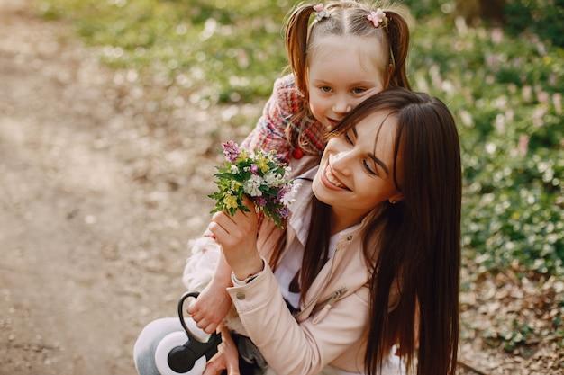 Madre elegante con la figlia in una foresta di estate