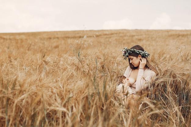 Madre elegante con la piccola figlia sveglia in un campo