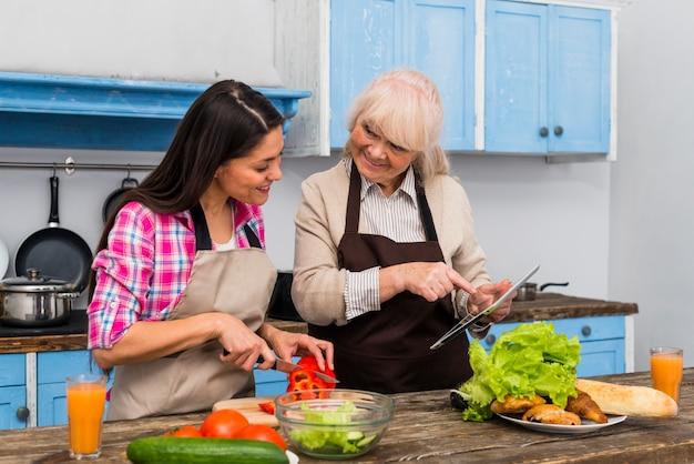 Madre felice che assiste la sua giovane figlia per preparare il cibo in cucina