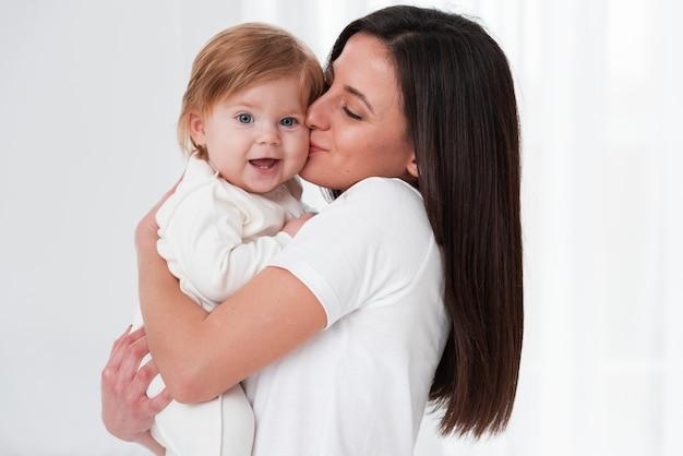 Madre felice che bacia bambino sorridente