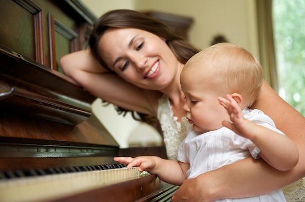 Madre felice che sorride mentre il bambino gioca il piano