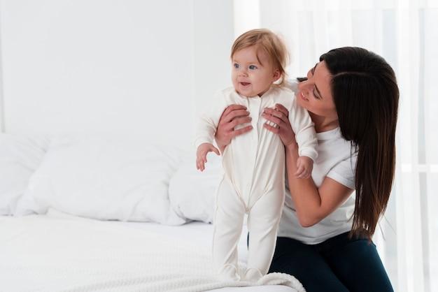 Madre felice che tiene bambino a letto