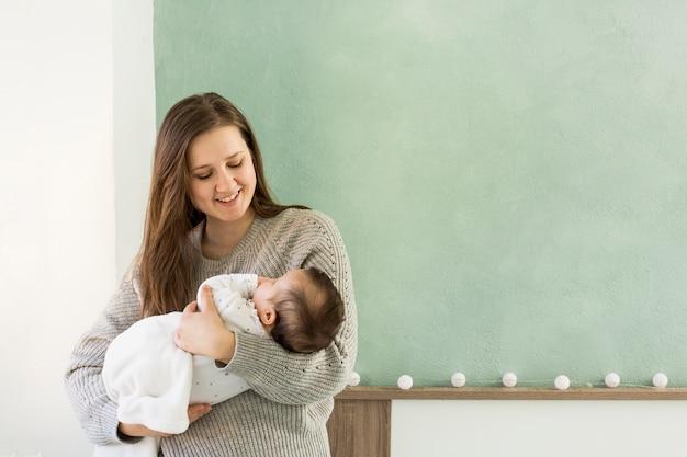 Madre felice che tiene bambino sveglio tra le braccia