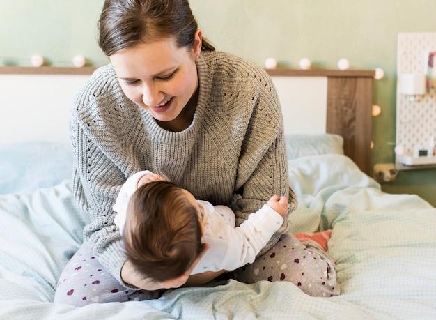 Madre felice che tiene bambino tra le braccia