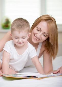 Madre felice con il libro di lettura del bambino a casa.