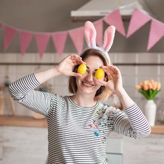 Madre felice con le orecchie del coniglietto che tengono le uova di pasqua