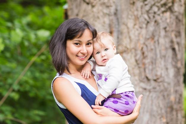 Madre felice di razza mista con ritratto di bambina all'aperto.