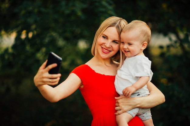 Madre felice e bambino prendendo un selfie