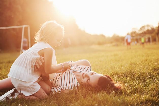 Madre felice e figlia che abbracciano in un parco al sole su un'estate luminosa di erbe.