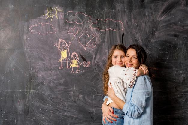 Madre felice e figlia che abbracciano vicino alla lavagna con disegno