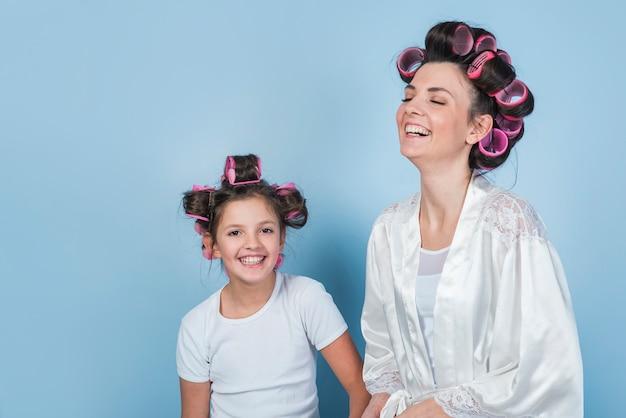 Madre felice e figlia nel sorridere dei bigodini