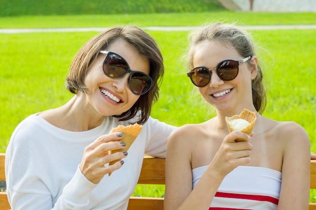 Madre felice e figlia sveglia che mangiano gelato