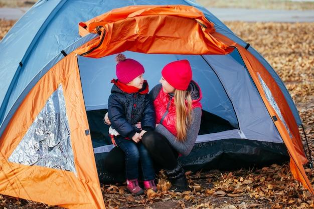 Madre felice e sua figlia che posano seduta in una tenda