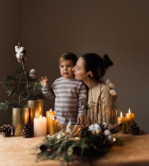 Madre felice e suo figlio con decorazioni natalizie. casa accogliente hygge. felice momento della maternità